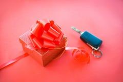 Geben Sie Geschenkauto Schlüsselkonzept rote Geschenkbox mit rotem Bandbogen und Schlüsselauto als Geschenk auf rotem Hintergrund stockbilder