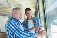 Geben Sie Glaser mit dem Lehrer in die Lehre, der Fenster am Standort installiert Lizenzfreie Stockfotos