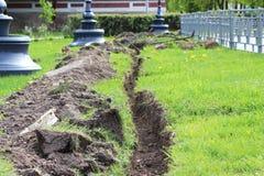 Geben Sie im Boden mit einem Graben um, der für das Kabel gegraben wird, das in die Stadt legt Lizenzfreies Stockfoto