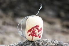 Geben Sie mit japanischem Charakter im Rot auf einem Strand Auftrieb Stockfotos