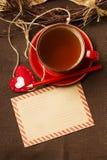 Geben Sie Umschlag, Tasse Tee und Dekorationen bekannt Lizenzfreies Stockbild