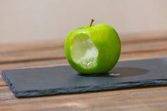 gebeten groene appel op zwarte steen stock foto's
