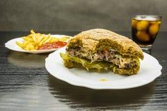 Gebeten rundvleeshamburger en frieten met ketchup en kola met I royalty-vrije stock fotografie