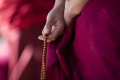 Gebetkorne in der Hand des Mönchs Stockfotografie
