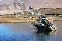 Gebetmarkierungsfahnen in einem See in Tibet Stockfoto
