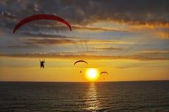 Gebetriebene Fallschirme über dem Meer Stockbild