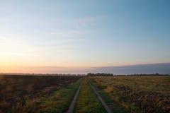 Gebied met een voetpad bij zonsondergang Royalty-vrije Stock Foto's