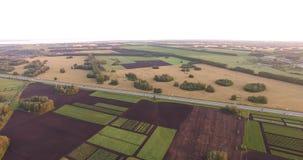 Gebieden voor akkerland en een weg bij zonsondergang stock footage