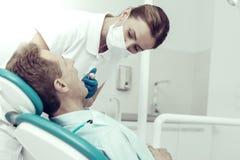 Gebildeter Spezialist, der die Zähne von ihrem Patienten kuriert lizenzfreie stockfotos