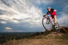 Gebirgs-Radfahrer-Reiten-donwhill gegen blauen Abendhimmel lizenzfreie stockfotografie