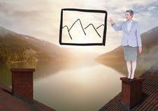 Gebirgsbild Zeichnung und Geschäftsfrau, die auf Dächern mit Kamin und Seeberglandscap stehen Lizenzfreie Stockfotografie