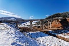 Gebirgsbrücke im Winter mit Schnee und blauem Himmel Lizenzfreies Stockfoto