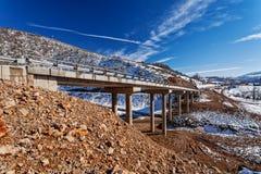 Gebirgsbrücke im Winter mit Schnee und blauem Himmel Lizenzfreie Stockfotos