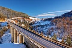 Gebirgsbrücke im Winter mit Schnee und blauem Himmel Stockbilder