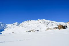 Gebirgschalet und schneebedeckte Spitzen Stockbilder