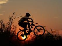 Gebirgsfahrrad-Rennläuferschattenbild Stockfotografie