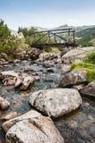 Gebirgsfluß und hölzerne Brücke Lizenzfreie Stockbilder