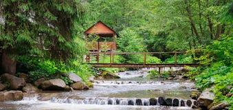 Gebirgsfluss, üppige Vegetation und Erholungsgebiet mit einer Brücke und einem Gazebo Standortplatz Karpaten, Ukraine, Europa wei stockbilder