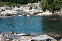 Gebirgsfluss, der in die grünen und felsigen Berge überschreitet Lizenzfreies Stockbild