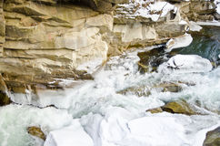 Gebirgsfluss, der schnell Lamai-Eis fließt und Steinfelsen abzieht stockfoto