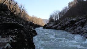 Gebirgsfluss, der unter den Felsen läuft stock footage