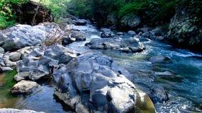 Gebirgsfluss mitten in Wald, in Tasikmalaya, West-Java, Indonesien Lizenzfreies Stockbild