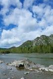 Gebirgsfluss unter blauem Himmel Stockfotos