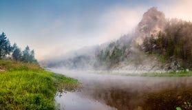 Gebirgsfluss unter Felsenwänden im Nebel Stockfotografie