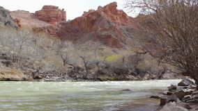 Gebirgsflussfl?sse unter den Steinen auf dem Hintergrund von roten Felsen stock footage