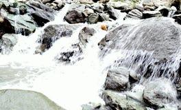 Gebirgsflussstrom des Wassers in den Felsen stockbild