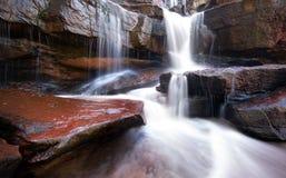 Gebirgsflusswasserfall, -felsen und -Trinkwasser Stockfotos