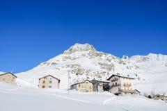 Gebirgshäuser und schneebedeckte Spitzen Stockfotos