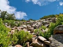 Gebirgshügel mit Steinen und blauem Himmel Stockfotografie