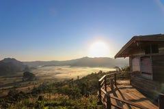 Gebirgshütte mit einem Bergblick bei Sonnenaufgang Stockfotografie