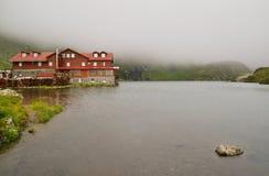 Gebirgshütte und -see Stockfotos