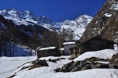 Gebirgshütten unter Schnee, italienische Alpen, das Aostatal. Stockfoto