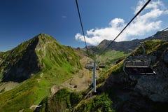 Gebirgskabelbahn, die unten über schöne Frühherbstberglandschaft ausdehnt stockfoto
