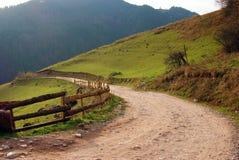 Gebirgslandschaft: gebogene landwirtschaftliche Straße Stockbild
