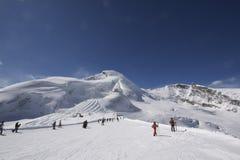 Gebirgslandschaft mit den Skifahrern, die weg Ski fahren Lizenzfreies Stockbild