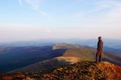 Mann, der auf einen Berg steht Lizenzfreies Stockfoto