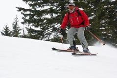 Gebirgsmann-Skifahrer, der unten die Steigung rollt Lizenzfreie Stockfotos