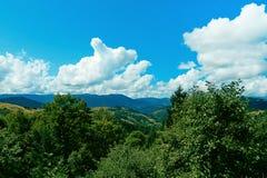 Gebirgsrücken mit Koniferenwaldgrünbergen und blauem Himmel mit weißen Wolken Große Berge Stockbild