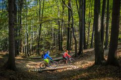 Gebirgsradfahrendes Frauen- und -mannreiten auf Fahrrädern am Sonnenuntergangberg lizenzfreie stockbilder