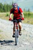 Gebirgsradfahrer auf landwirtschaftlicher Straße Lizenzfreies Stockfoto
