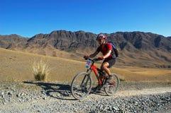 Gebirgsradfahrer, der in der Wüste läuft Lizenzfreies Stockfoto