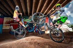 Gebirgsradfahrer, die Wheeliebremsung auf einem mtb Fahrrad tun Lizenzfreie Stockbilder