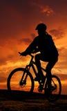 Gebirgsradfahrerschattenbild im Sonnenaufgang Stockfotografie