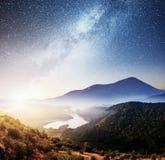 Gebirgsschöne Landschaft mit Flussansichten, vibrierender nächtlicher Himmel stockfotografie