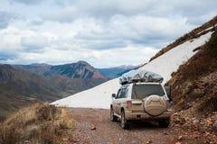 Gebirgsschnee-Straßenlandschaft Auto des Jeeps 4x4 auf einem Gebirgspass, Bergspitze Ende der Straße in den Bergen Straßenblockie Lizenzfreies Stockbild