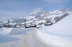 Gebirgsschneebedeckte Straße und -dorf in einer alpinen Landschaft der Landschaft Stockfotografie